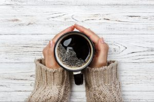 Woman holding cup of hot coffee on rustic wooden table, closeup photo of hands in warm sweater with mug, winter morning concept, top view. Banner.